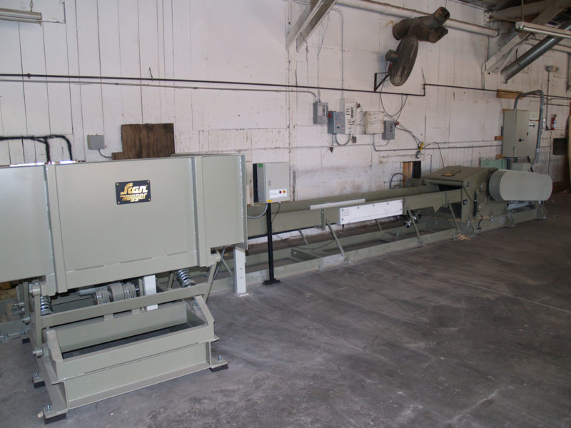 Small Vibration Table Feeding A Vibration Conveyor With Metal Detection Segment Feeding Into Wood Chipper Inside A Production Hall