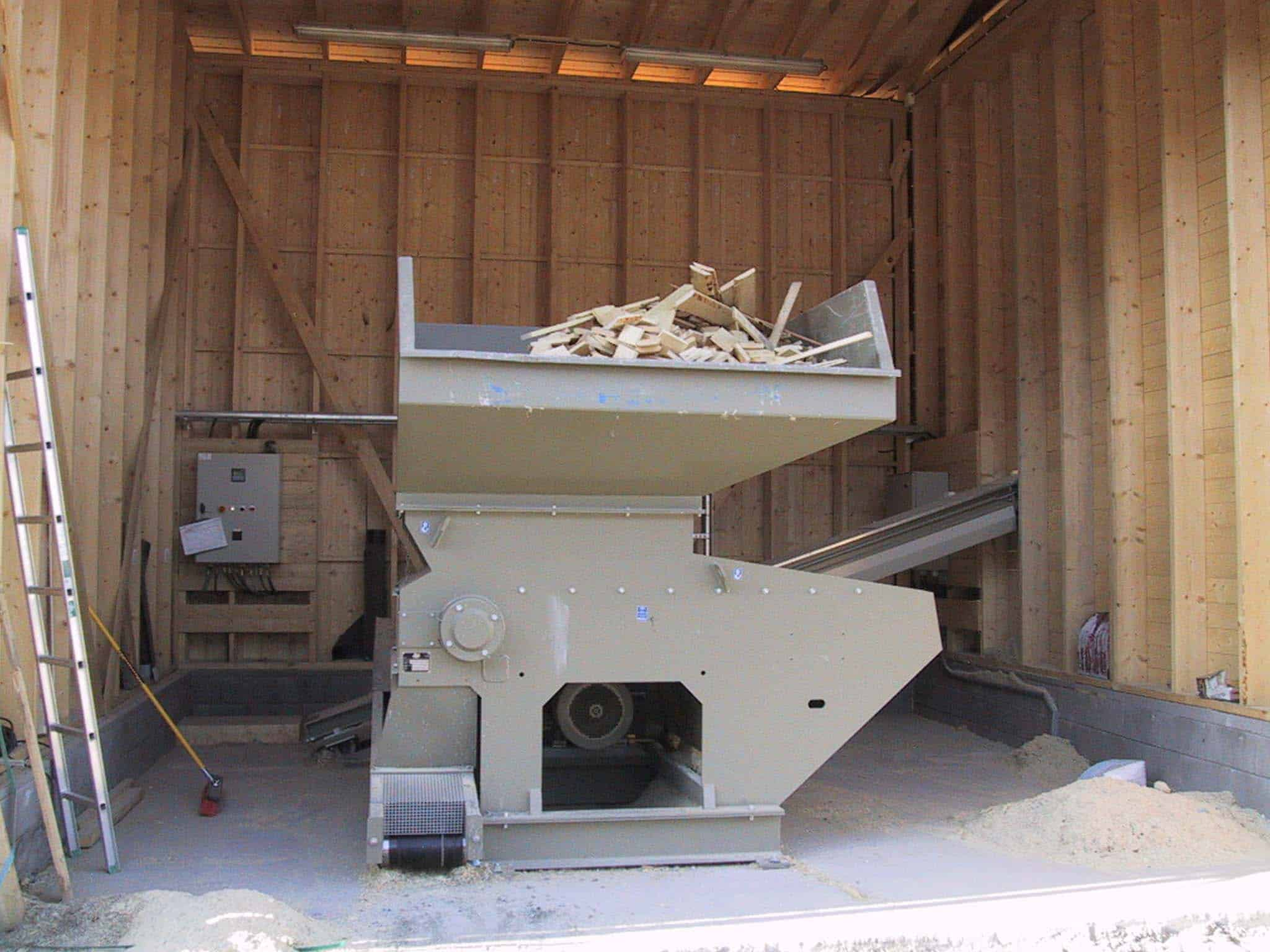 Scanhugger wood waste recycling shredder in barn loaded with wood